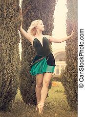 Beautiful ballerina stands among tall shrubs