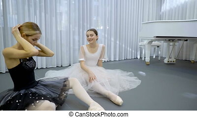 Beautiful ballerinas are talking in ballet studio indoors....