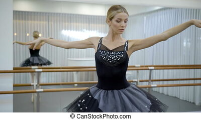 Beautiful ballet dancer is turning with body in ballet school indoors.