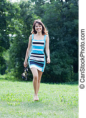 barefoot woman walking on lawn