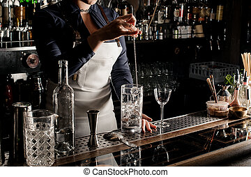 Beautiful barman woman stirring fresh summer drink in a...