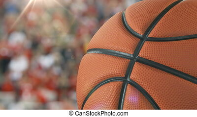 Beautiful Basketball Ball Rotating Close-up in Slow Motion on Stadium Background with Flare. Looped Basketball 3d Animation of Turning Ball. 4k UHD