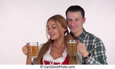 Beautiful Bavarian couple celebrating Oktoberfest, drinking beer together
