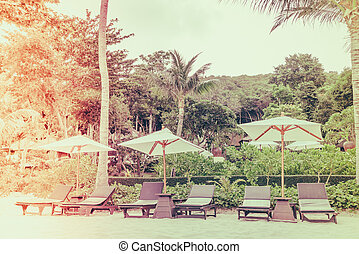 Beautiful beach chairs with umbrella on tropical white sand beach - Filtered image processed vintage effect