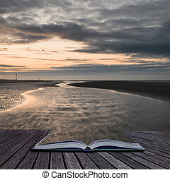 Beautiful beach coastal low tide landscape image at sunrise with colorful vibrant sky coming out of pages of book