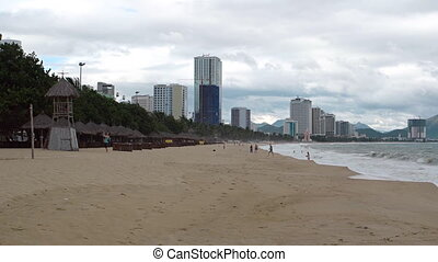 Beautiful beach in Nha Trang, with highrise buildings in the...