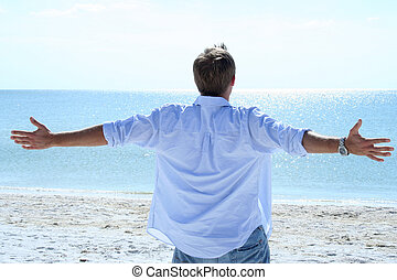 Beautiful Beach - Man lifting his arms out to sides looking...