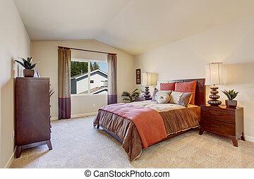 Beautiful bedroom with bright orange bedding