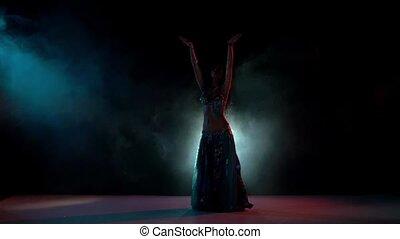 Beautiful belly dance movement, slow motion, in smoke, black