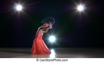 Beautiful belly dancer girl continue dancing exotic dance on black, back light, slow motion