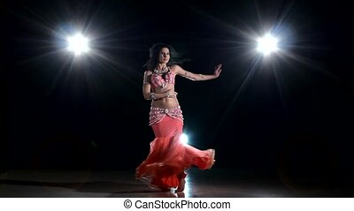 Beautiful belly dancer girl dancing exotic dancce on black, back light