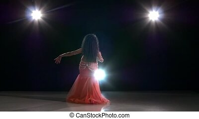 Beautiful belly dancer girl dancing exotic dancce on black, back light, slow motion