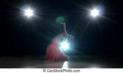 Beautiful belly dancer girl dancing exotic dance movement on black, back light