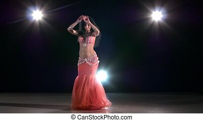 Beautiful belly dancer girl dancing exotic dance movement on black, back light, slow motion