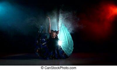 Beautiful belly dancer girl dancing exotic dance movement on black, smoke, back light