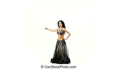 Beautiful belly dancer with dark hair dancing and shaking her hips, on white, slow motion