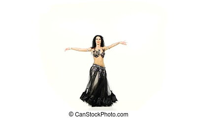Beautiful belly dancer with dark hair smiling and dancing, shaking her hips, on white, slow motion