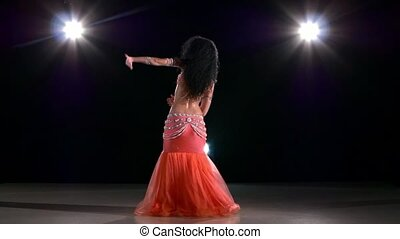 Beautiful belly dancer woman dancing exotic dancce on black, back light, slow motion