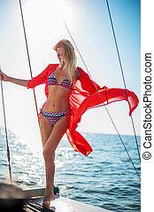 Beautiful bikini girl in open water sea on yacht