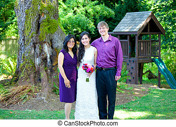 Beautiful biracial bride standing with her parents. ...