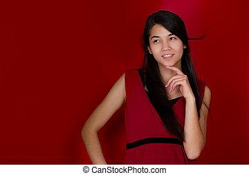 Beautiful biracial teen girl hand on chin thinking. Red backgrou