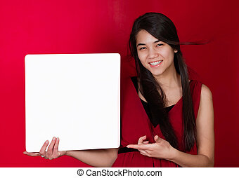 Beautiful biracial teen girl holding up square white sign, point