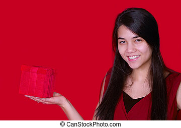 Beautiful biracial teen girl in red dress holding red present on