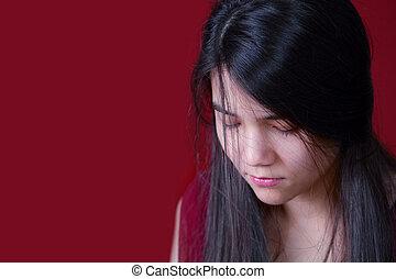 Beautiful, biracial teen girl looking down, depressed or sad, on