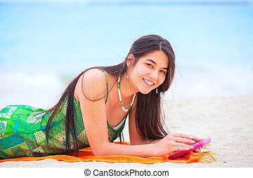 Beautiful biracial teen girl lying on tropical beach with phone