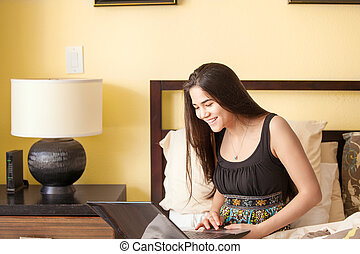 Beautiful biracial teen girl on bed looking at laptop