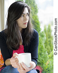 Beautiful biracial teenage girl or young woman holding coffee cup by window, sad or thoughtful expression