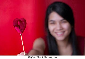 Beautiful biracial young teen girl holding heart balloon, smilin