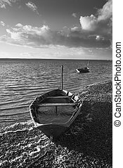 Beautiful black and white sunset landscape image of boats moored in Fleet Lagoon in Dorset England