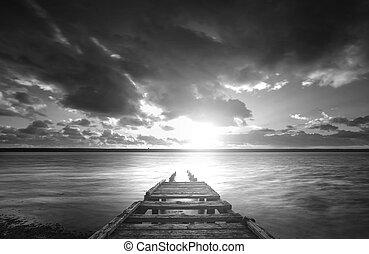 Beautiful black and white sunset landscape image of Fleet Lagoon in Dorset England