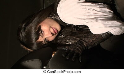 Beautiful Black-Haired Woman In Car Posing For the Camera