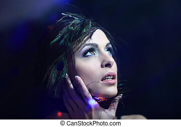 Beautiful black-haired woman with peacock feathers in studio sho