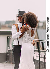 Beautiful black newlyweds softly hugging on the rooftop