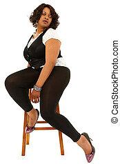 Beautiful Black Plus Sized Woman sitting on stool over white background.