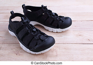 Beautiful black Shoe leather sandals suitable for adventure. isolated on wooden background