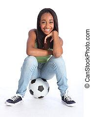 Beautiful black soccer player girl sitting on ball