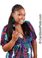 beautiful black woman holding sunglasses