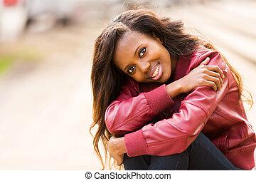 black woman sitting outdoors