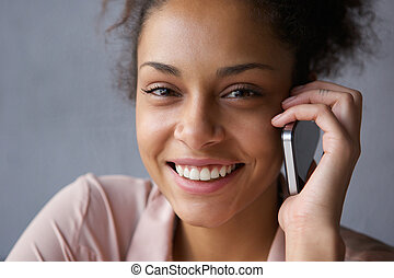Beautiful black woman smiling with mobile phone