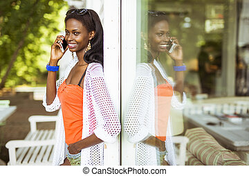 Beautiful black woman talking on phone and smiling during a ...