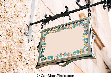 Beautiful blank board of a fancy shape hangs in a forged frame on the facade of a building