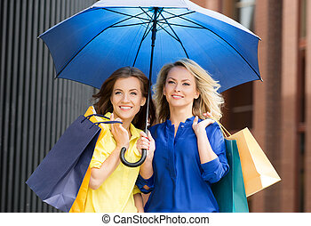 Beautiful blond and brunette with blue umbrella