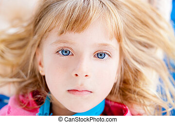 Beautiful blond blue eyes girl lying