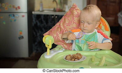 Beautiful blond boy sitting at a table and eating hamburger