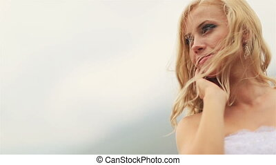Beautiful blond bride softly touching her face close up