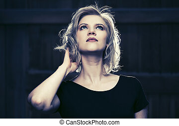 Beautiful blond fashion woman in black dress looking up